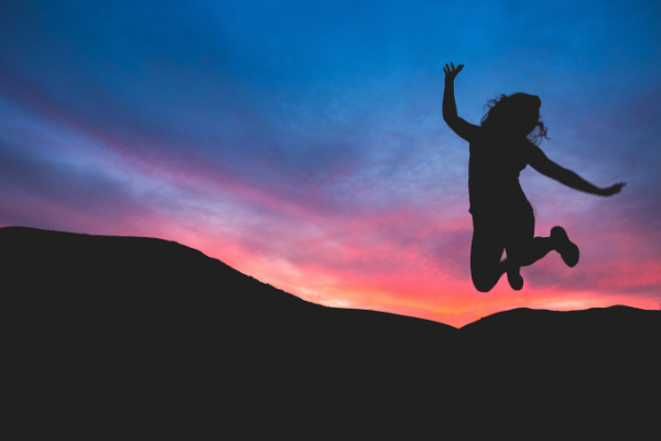 Person leaping for joy against a sunset
