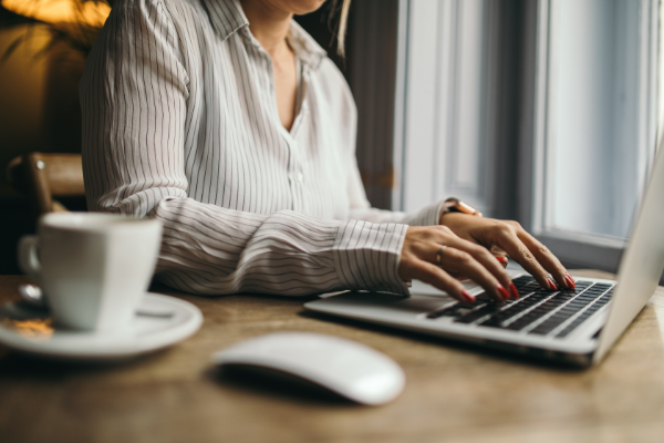 A woman typing with a cup of coffee. Another Portfolio Executive