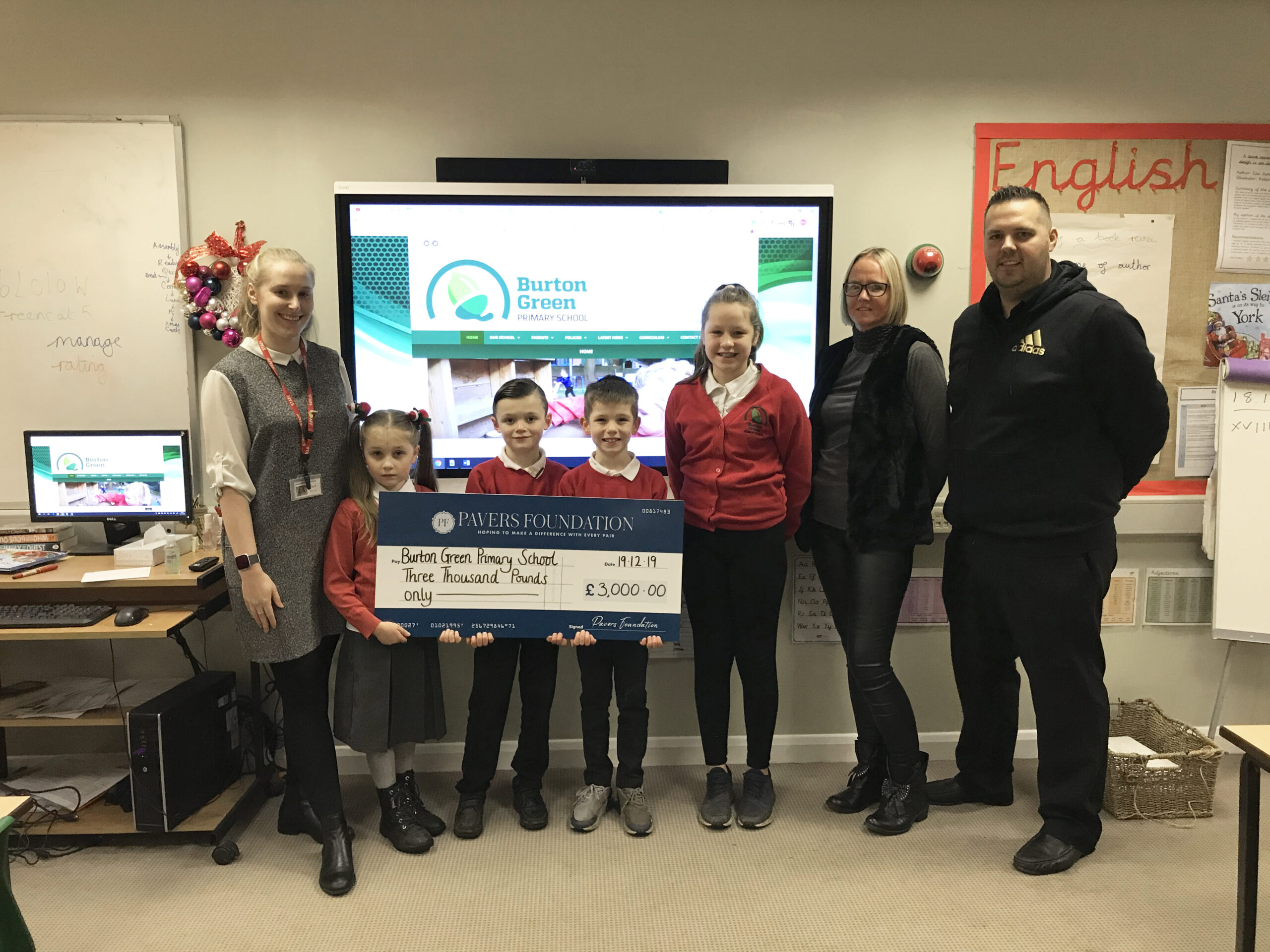 Ms Tutill, teacher at Burton Green Primary School and pupils from her class, receiving the donation presentation cheque.