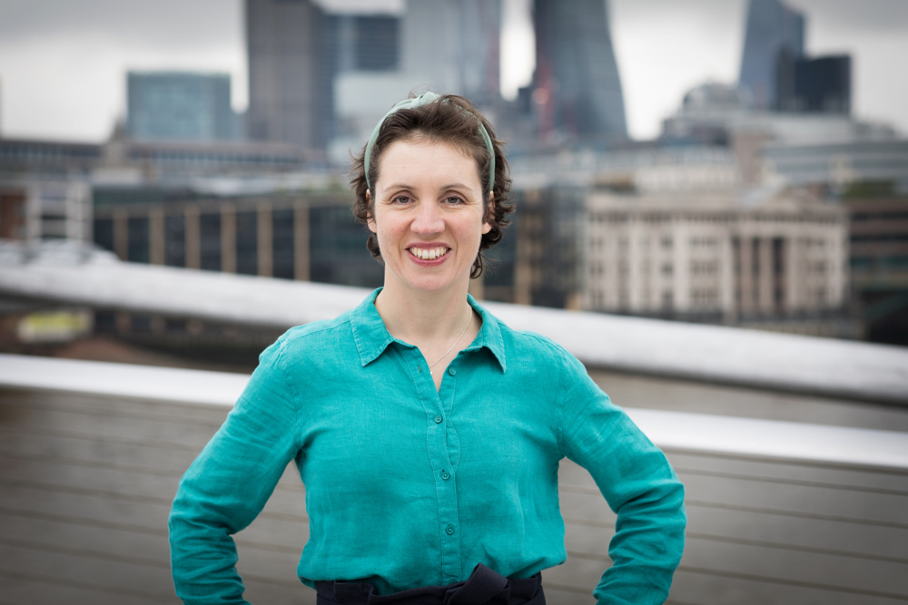 Bianca Sainty, stress-free health and fitness coach, is standing on the Millennium Bridge with the City of London in the background, smiling at the camera after delivering a workplace wellbeing workshop.