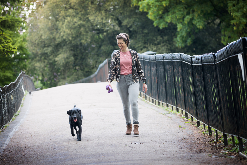 Bianca Sainty, Stress-free fitness coach, is walking in down a path in the park with her black Labrador. She is looking down at her dog and smiling.