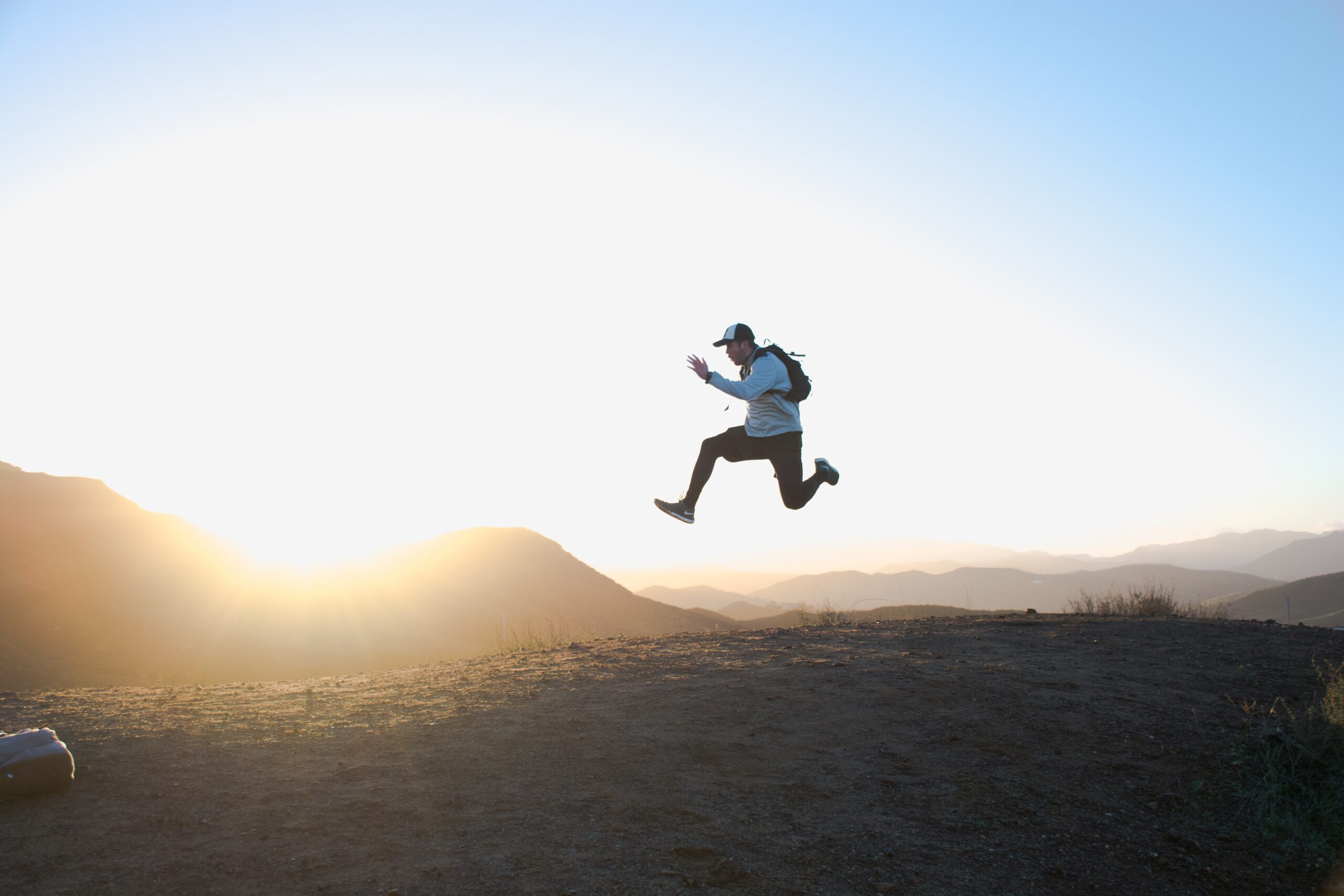 man jumping in the air in front of a sunset