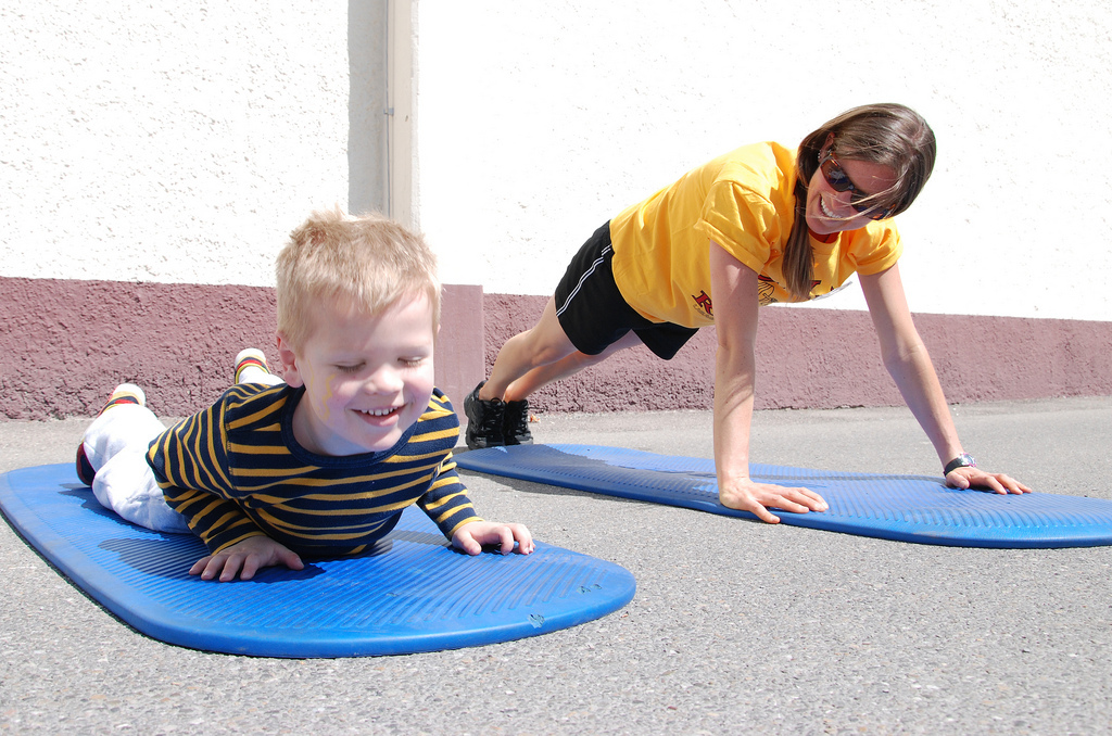 Caitlin Smith, CYS Services Acting Director of Sports and Fitness exercises with an unidentified boy during April's Month of the Military Child