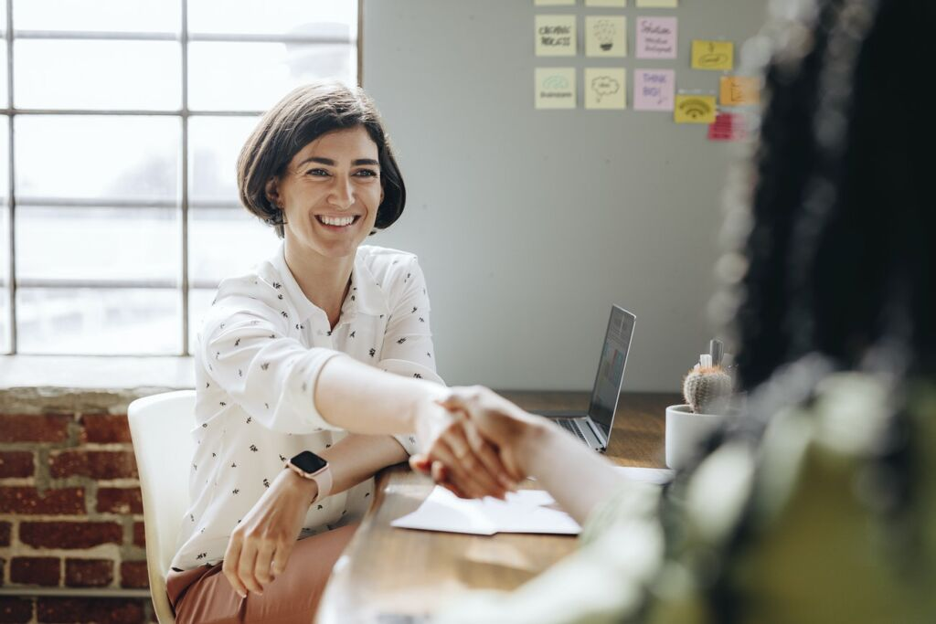 A woman at a desk with a laptop is greeting another person that's blurred out with a handshake - business etiquette in France