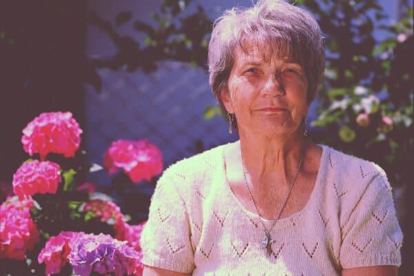 mujer con flores detras