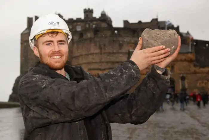 Archaeologist Samuel Kinirons with the stone catapult ball believed to have been fired during the siege of Edinburgh Castle.