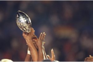 Players for the Denver Bronco players hold up the Lombardi Trophy after winning the Super Bowl XXXIII.