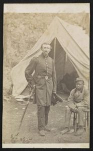 Major Luzerne Todd of Co. D, 23rd New York Infantry Regiment and Co. B, 86th New York Infantry Regiment in uniform with sword and unidentified young African American servant in front of a tent.