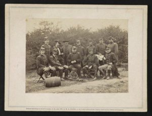 Photograph shows a group portrait of Generals Andrew A. Humphreys, Henry W. Slocum, William B. Franklin, William F. Barry, and John Newton, with an African American boy at Cumberland Landing, Virginia.