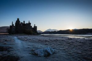 An astounding view of Kilchurn Castle standing alone on the long peninsula and surrounded by the wilderness.