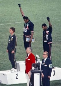 PUMA sponsored Gold medalist Tommie Smith (center) and bronze medalist John Carlos (right) showing the raised fist on the podium after the 200 m race at the 1968 Summer Olympics; both wear Olympic Project for Human Rights badges.