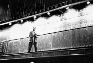 Unidentified man standing in front of a 'Trade' board on which he records a 'Market Score' at the Chicago Board of Trade. Photography by S. Kubrick.