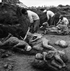 Archaeological workers extract the mummified bodies of two adults and three children from earthen molds on May 1, 1961.