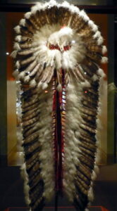 National Cowboy & Western Heritage Museum ( Oklahoma City ). Cree trailer headdress ( ca. 1940 ), made of red wool cloth, ribbon, eagle feathers, plume feathers, glass beats, raw hide and felt head