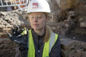 An archaeologist holding part of a money pot found on site at the Boar's Head.