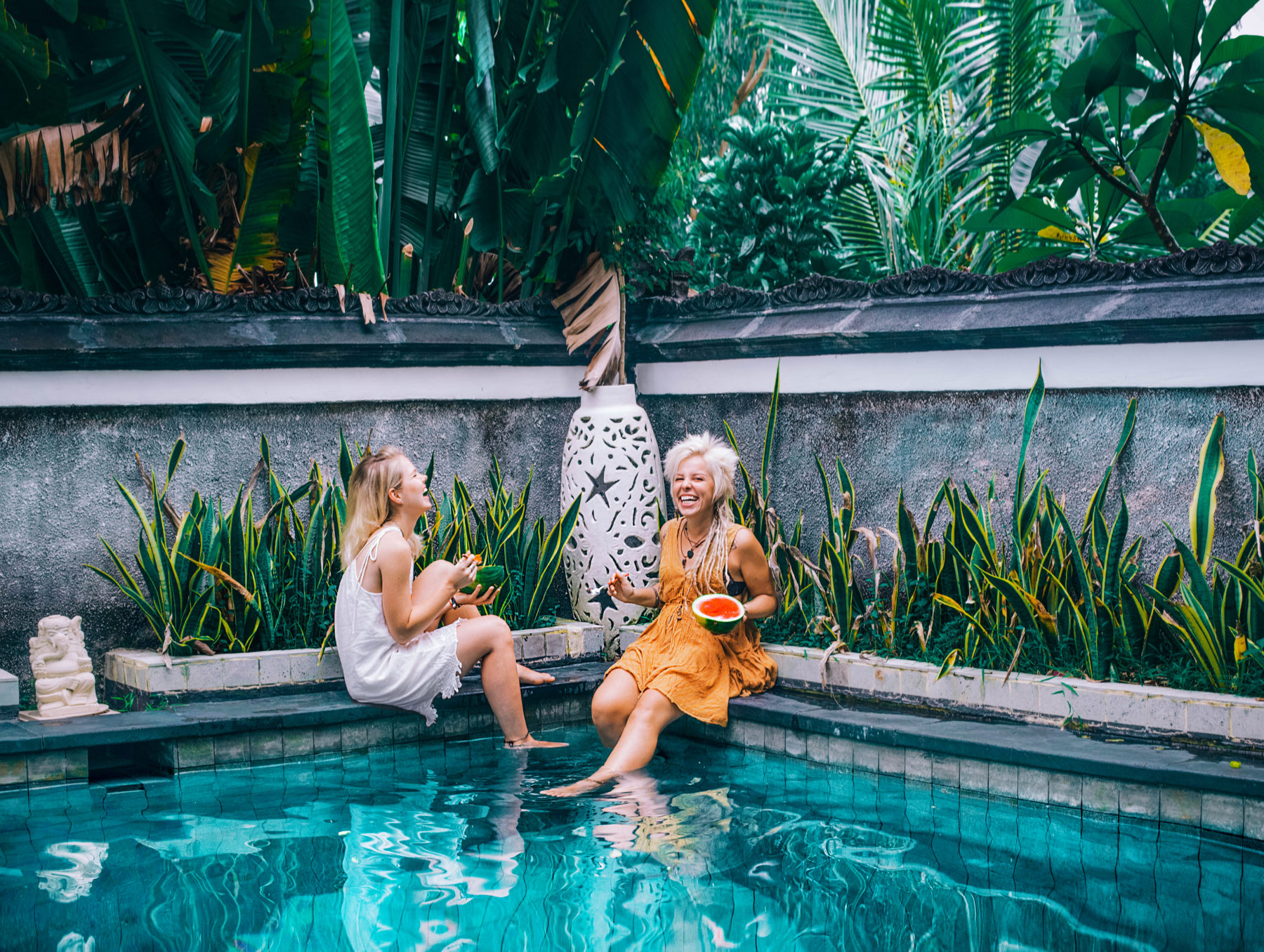 bali friends enjoying life and fresh fruit by the pool while on holidays in indonesia