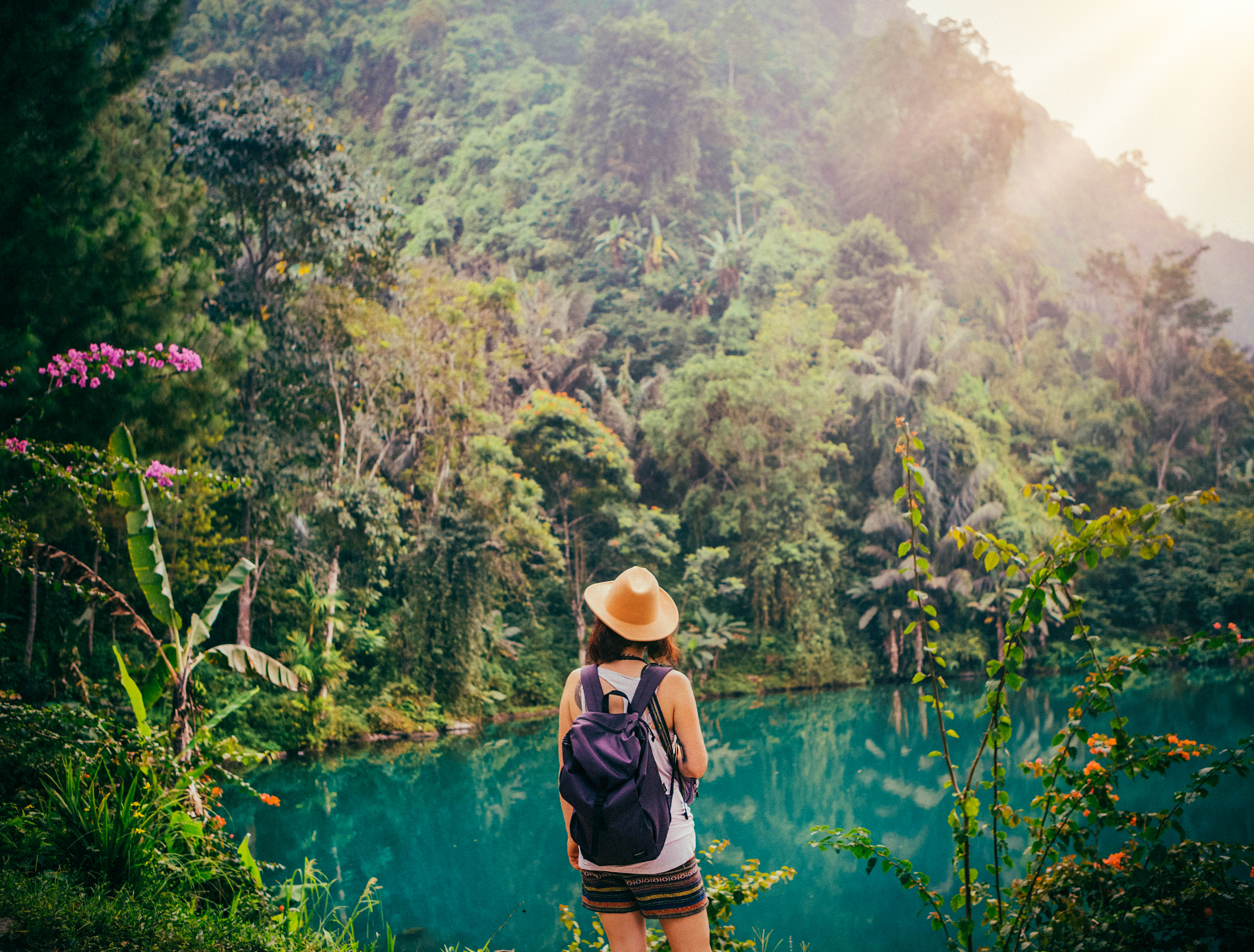 admiring indonesian jungle lush green plants water hat backpack next to waterfall tips java island