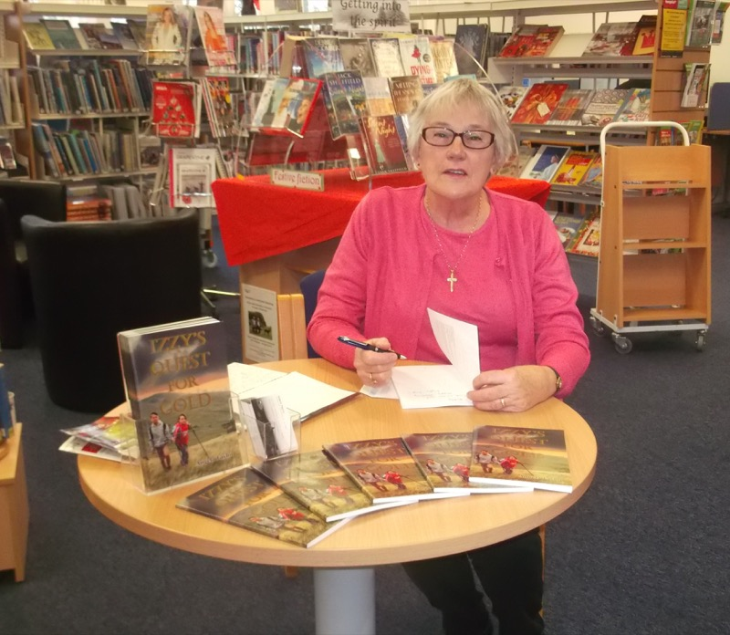 Photo of author Angela Taylor seated in front of book displays in her local library. Angela is signing copies of her book Izzy's Quest for Gold.
