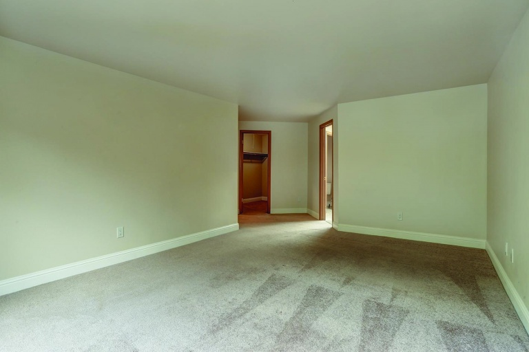 Empty bedroom of a luxury home with carpet floor.