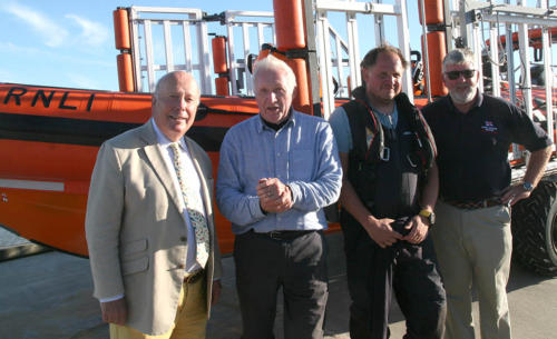 Journalist and broadcaster David Dimbleby sailed into Lyme unexpectedly with his son Henry during Lifeboat Week, pictured with celebrity guest Lord Julian Fellowes and lifeboat operations manager Nick Marks (photo by Richard Horobin)