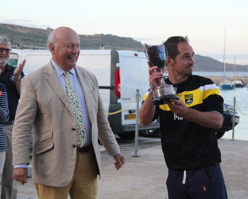 Mark Bailey picks up a trophy for Lyme Regis Football Club from Lord Julian Fellowes after winning the tug o' war