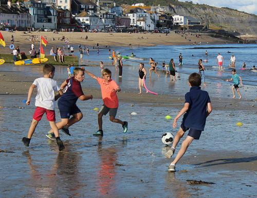 Children play football on the beach