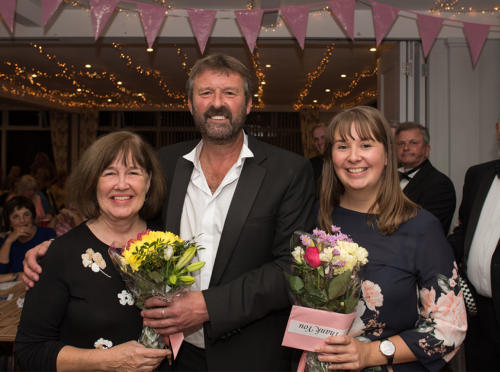 Lee Caddy hands flowers to Jackie and Francesca Evans for their work with Cancer Research UK