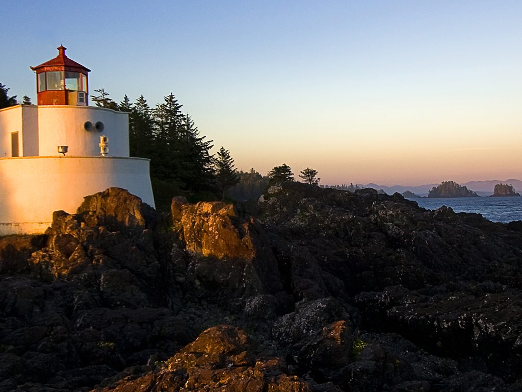 Photograph of a lighthouse surrounded by trees and overlooking the sea.