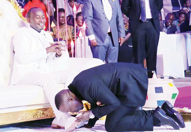 Joseph Kabuleta is kissing Prophet Mbonye