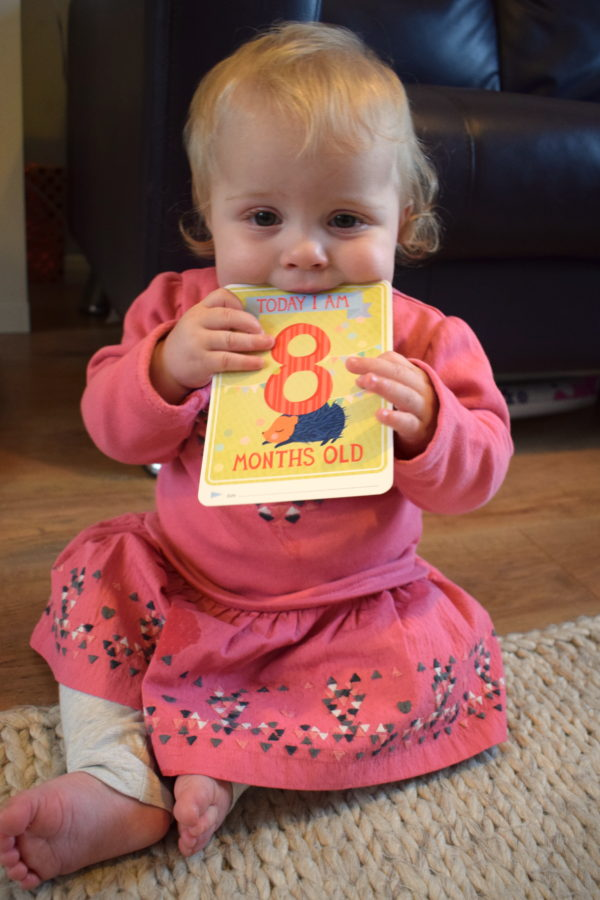 baby girl in pink top sitting up and biting a milestone card saying today I am eight months old