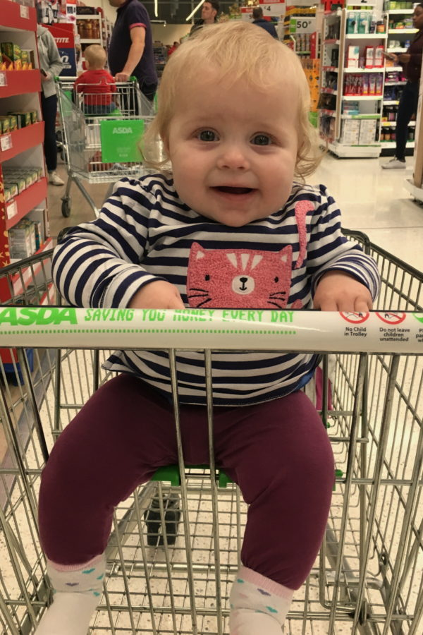 baby in a stripey top, sitting in supermarket trolley, smiling