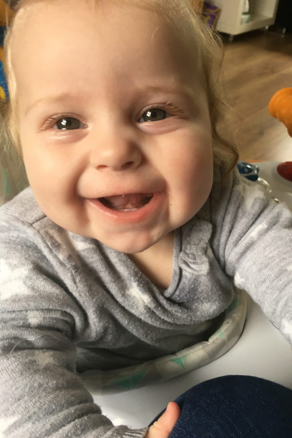 nine month old baby girl, in walker, looking up and laughing