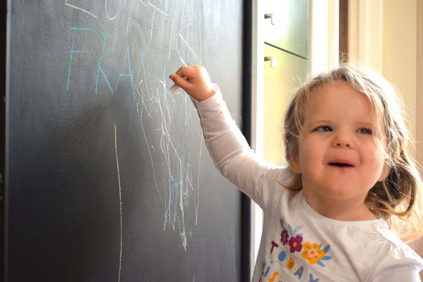 Toddler writing on blackboard wall at Center Parcs Elveden Forest