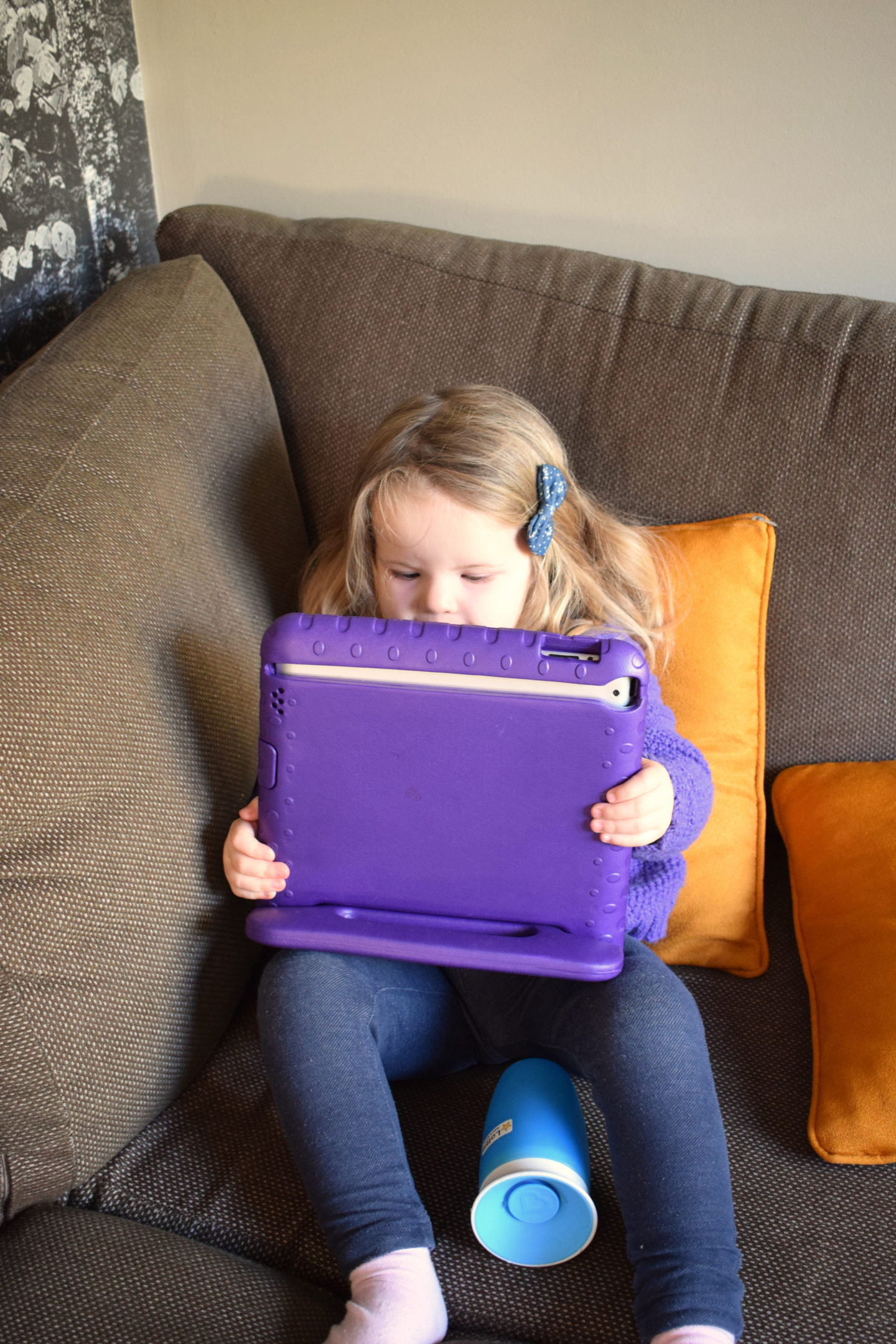 two year old girl watching ipad on the sofa at Center Parcs Elveden Forest