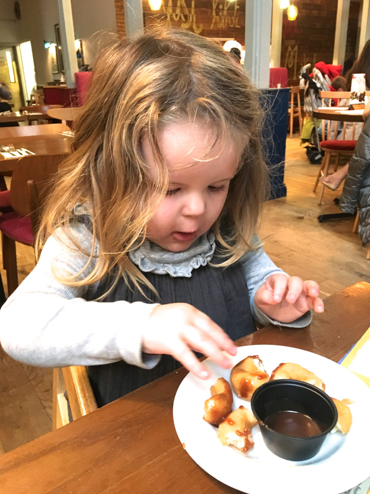 two year old girl eating pudding atBella Italia Center Parcs Elveden Forest