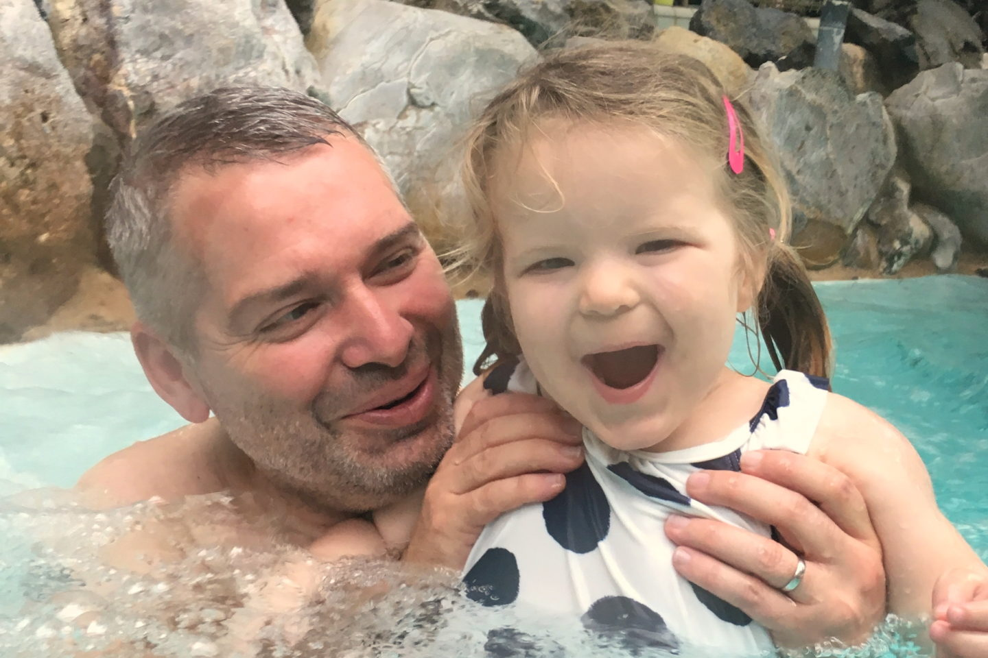 two year old swimming with dad smling at Center Parcs Elveden Forest