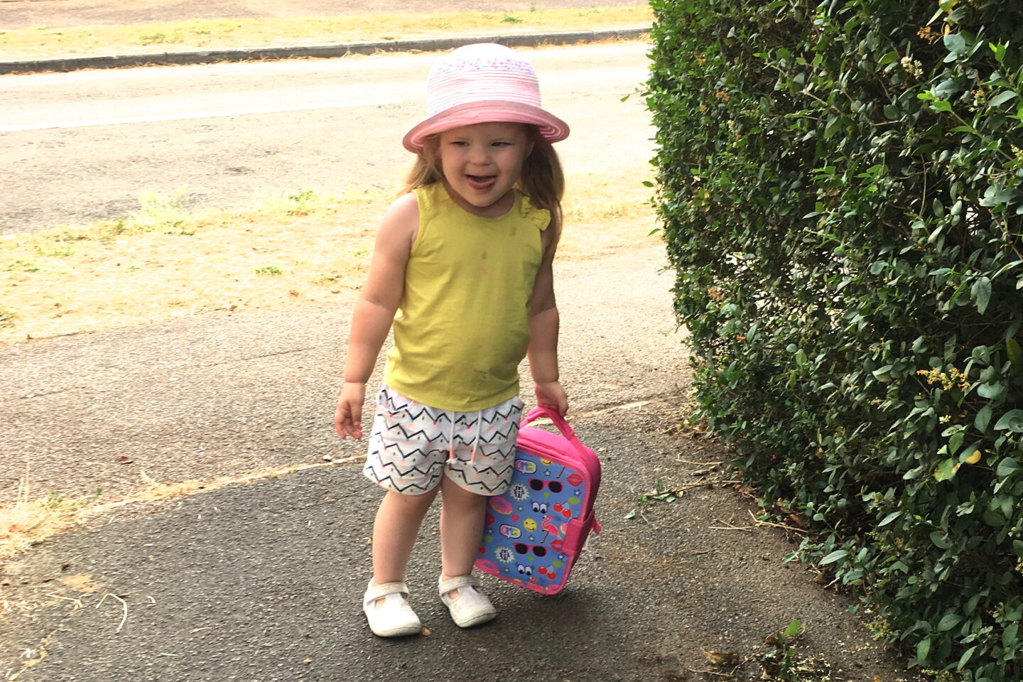 toddler girl in sunhat, holding lunch bag for weekly gratitude