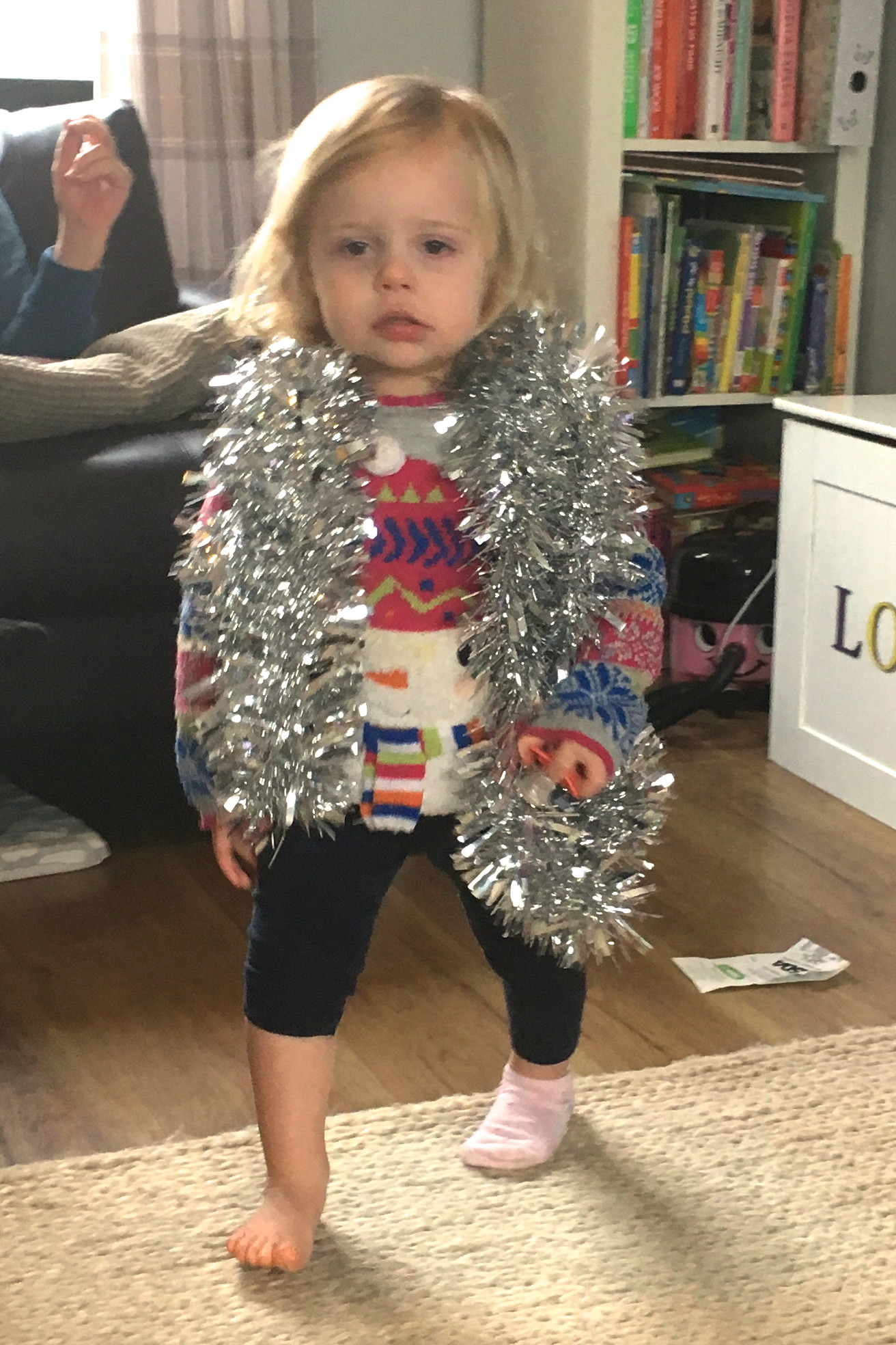 22 months old girl with tinsel around her shoulders