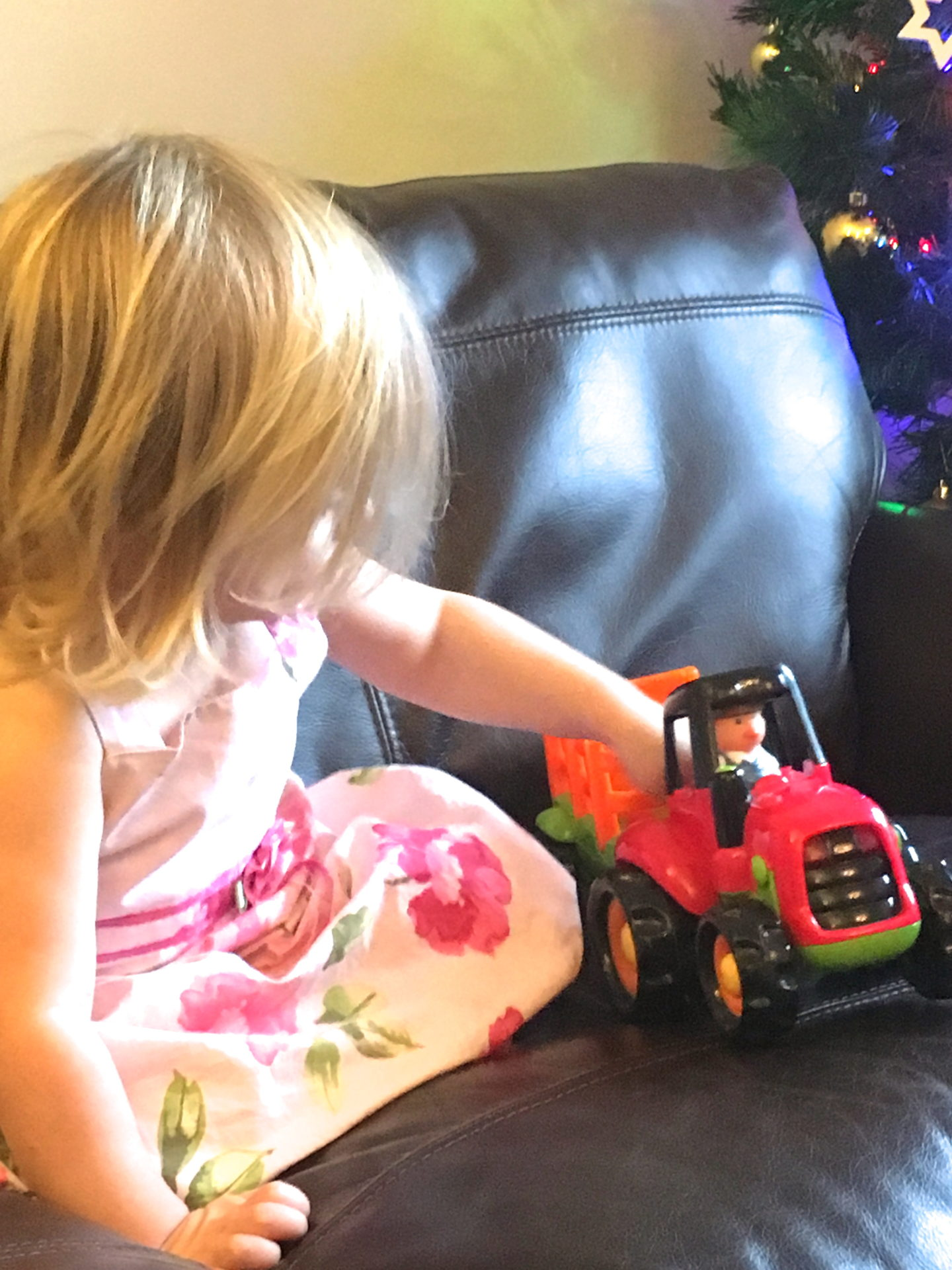 22 month old in pink dress playing with tractor toy