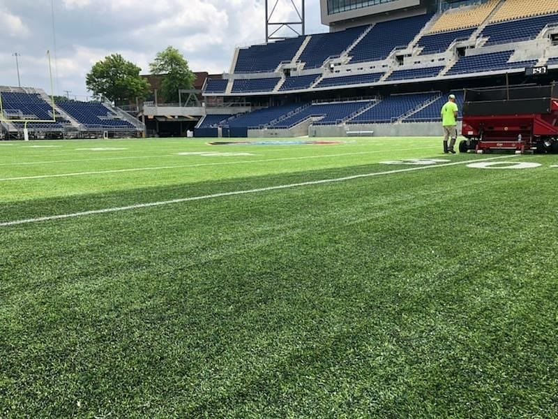 Football pitch with stands, made from artificial grass