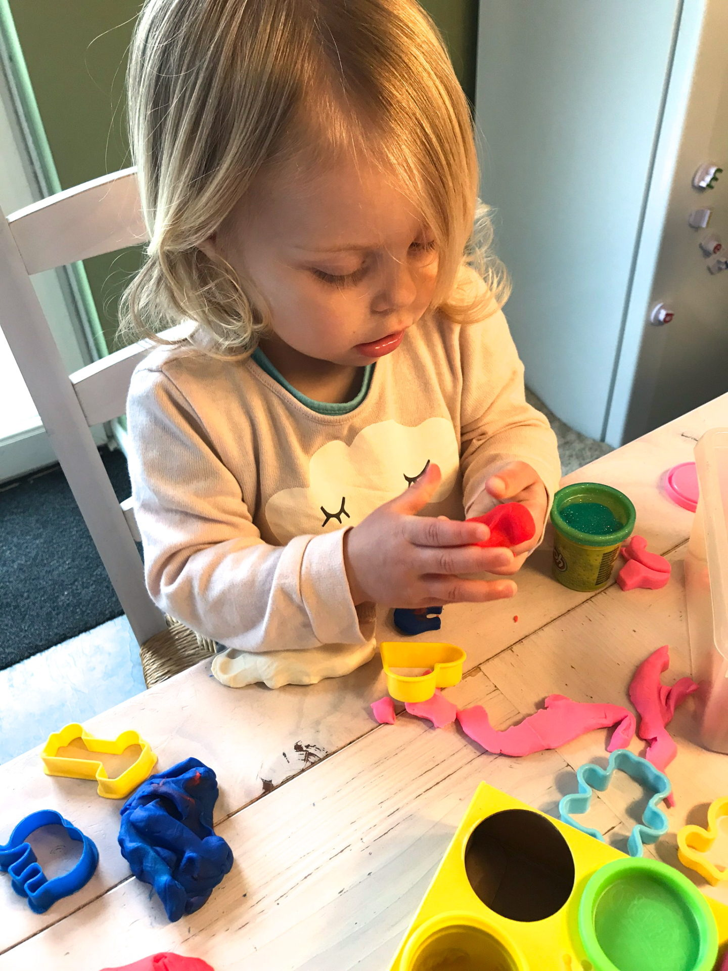 Two year old sitting at a table, playing with Play Doh