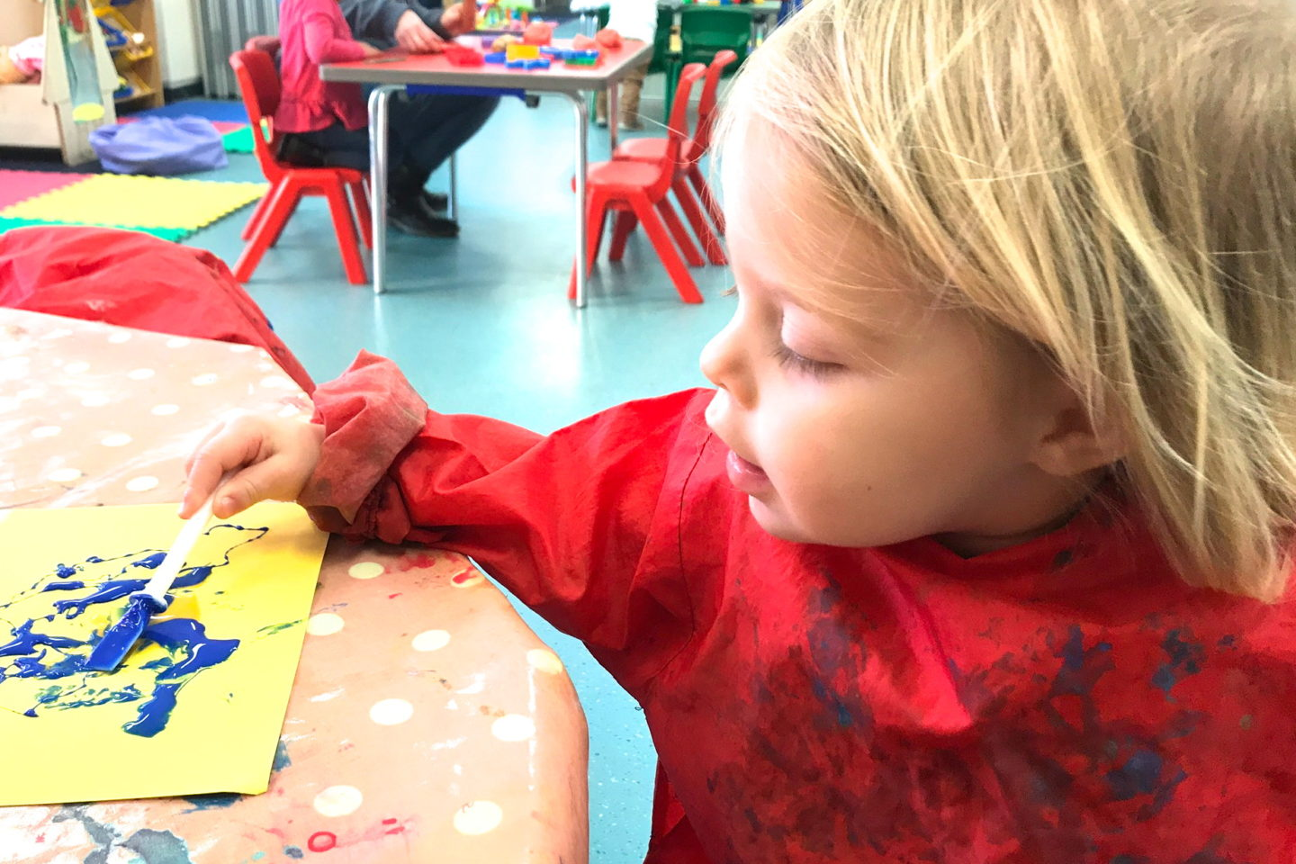 Two year old in an apron, painting
