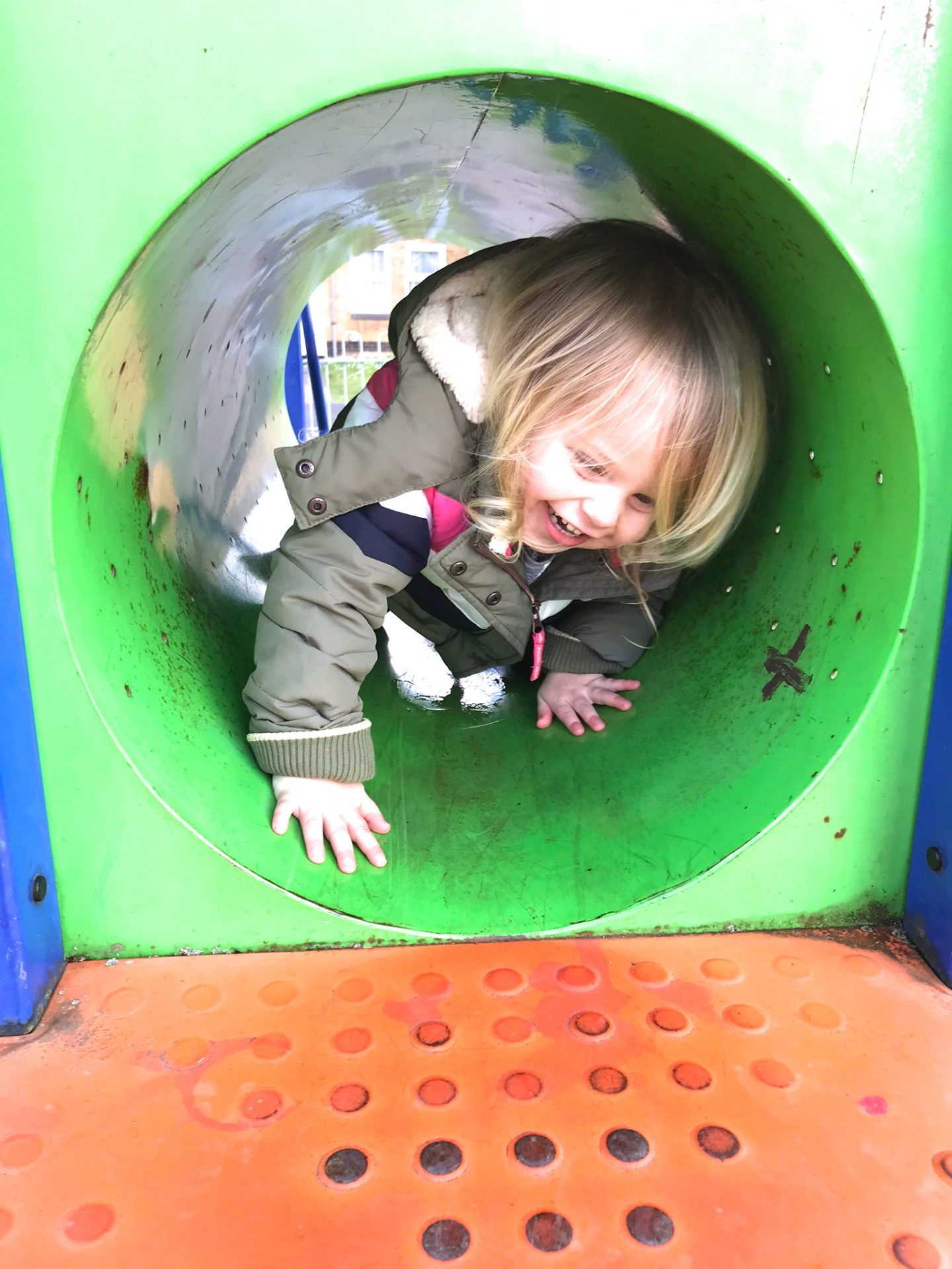 Two year old crawling through a tunnel in a playground