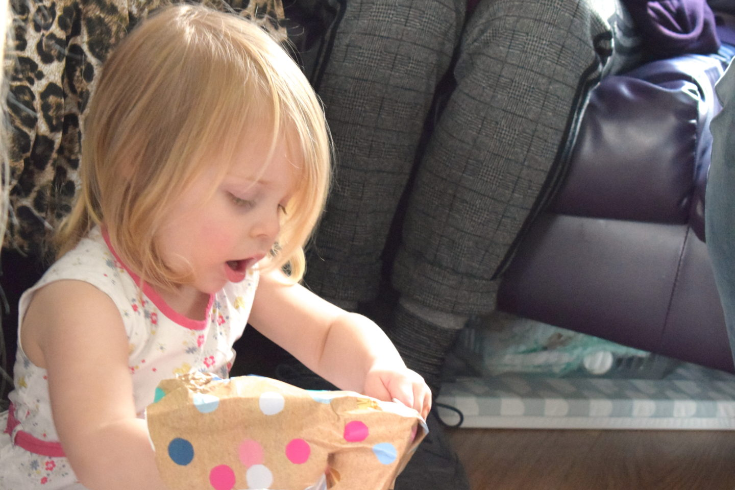 Two year old in a party dress, opening a present