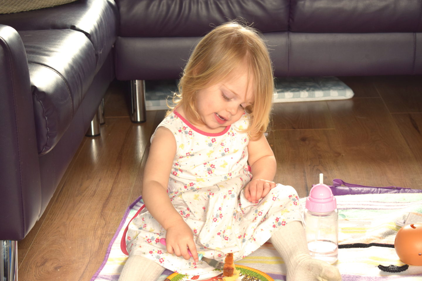 Two year old in a party dress, eating lunch on the floor