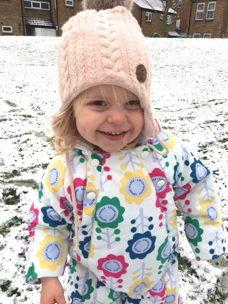 Two year old in snowsuit and woolly hat in a snowy firld