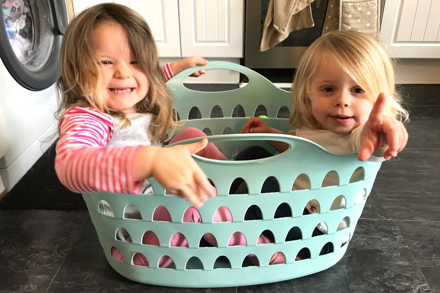two sisters sitting in a washing basket, laughing