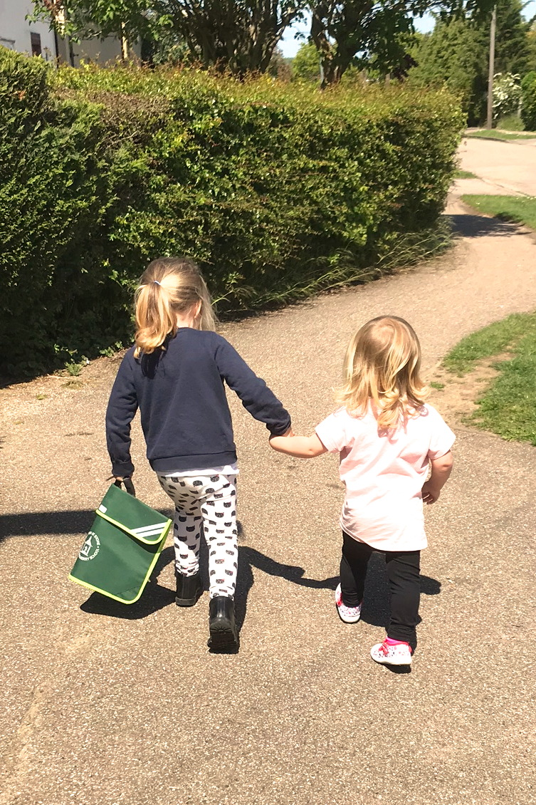 two girls hand in hand from behind, walking down a pavement