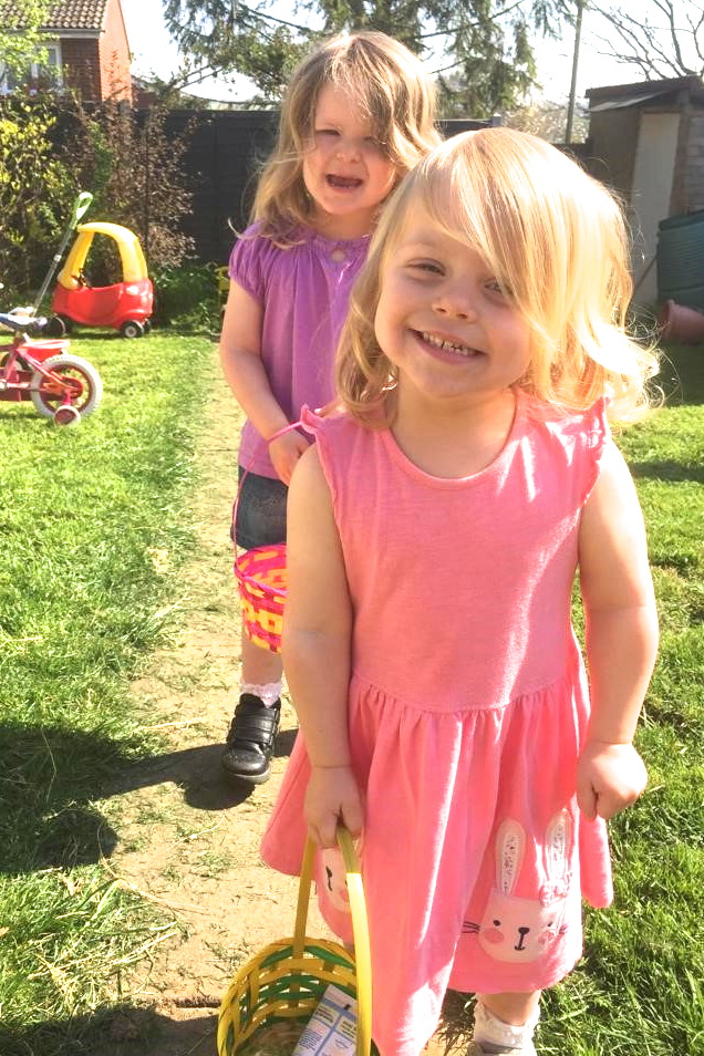 two young sisters holding baskets doing an easter egg hunt in the garden