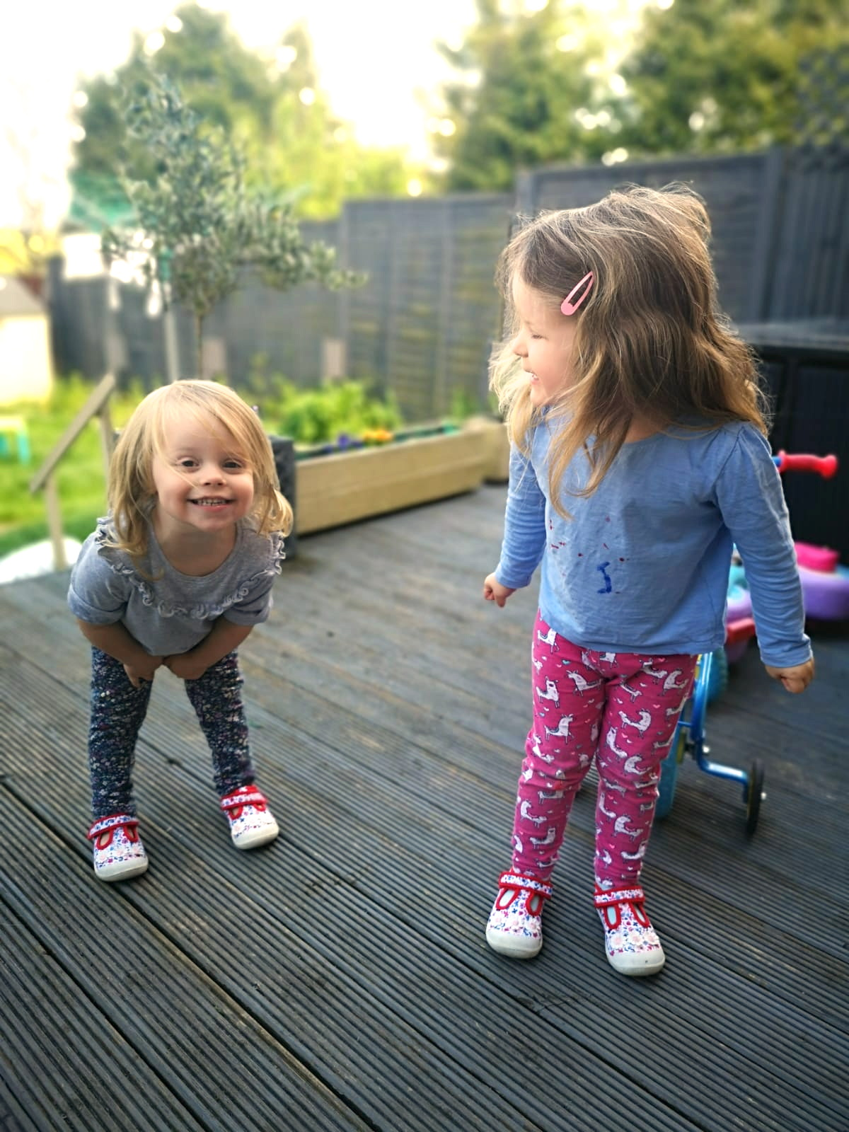 two young sisters playing in the garden